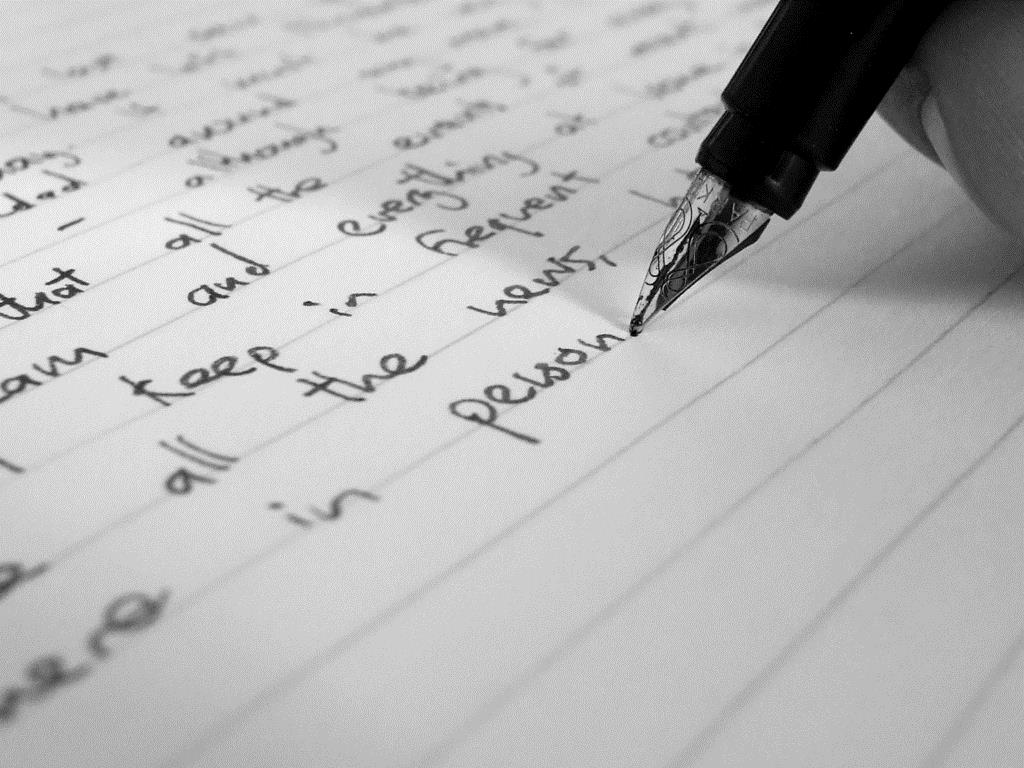 An image of a pen resting on a page of writing